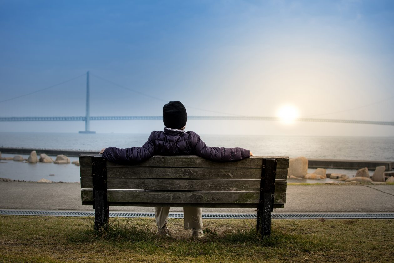 man sitting on bench looking at sun and sea